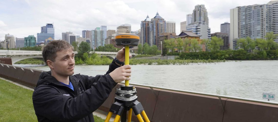 A man sets up a Hemisphere S631 GNSS Receiver in front of a city.