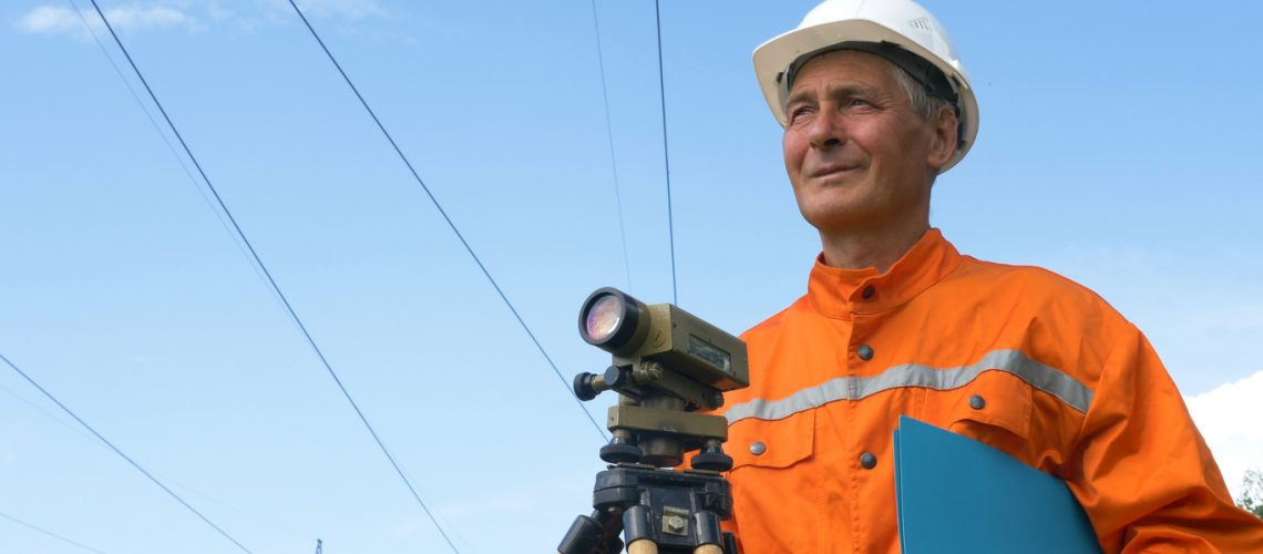 experienced survey specialist stands near dumpy level